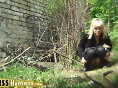 Blonde in black outfit pissing outdoors