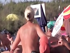 French naturist woman strokes cocks of two men on nudist beach